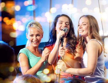 three happy women singing on night club stage